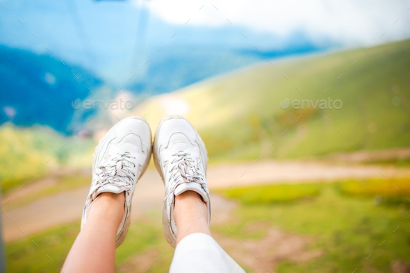 Close-up of female legs in sneakers on the grass outdoors in the park - Stock Photo - Images