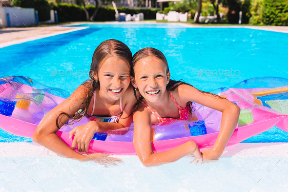 Adorable little sisters play in outdoor swimming pool - Stock Photo - Images