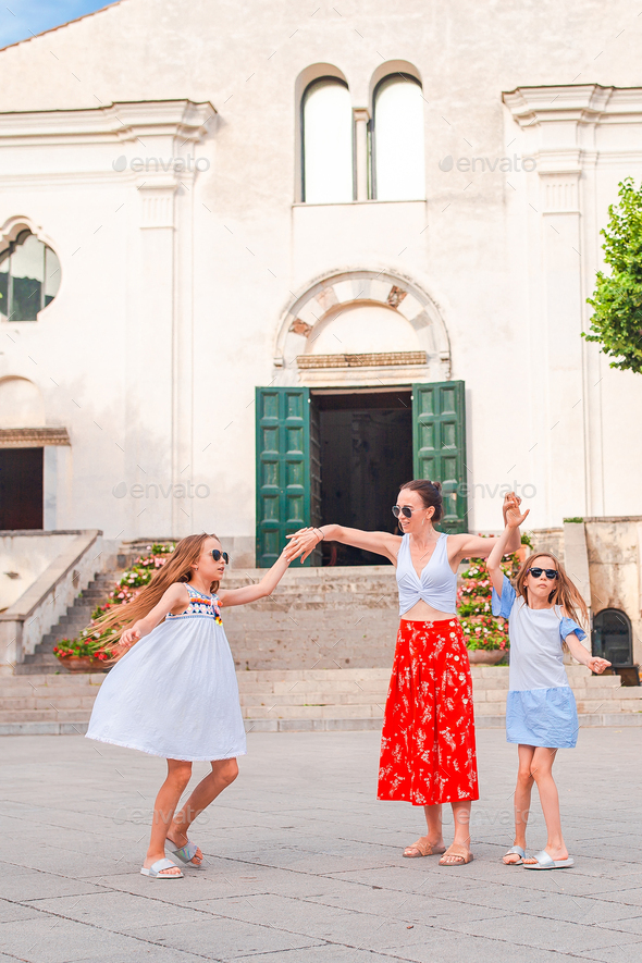 Adorable little girls and young mother have fun in italian old village - Stock Photo - Images