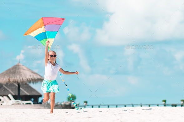 Little girl flying a kite on the beach with turquiose water - Stock Photo - Images