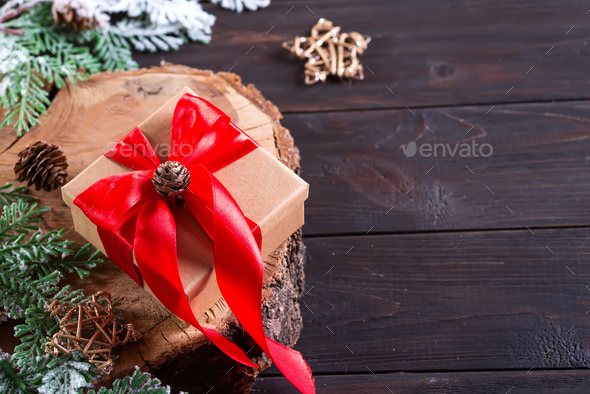 Brown gift box with red bow, christmas decoration on a wood cutting board on dark wooden background - Stock Photo - Images