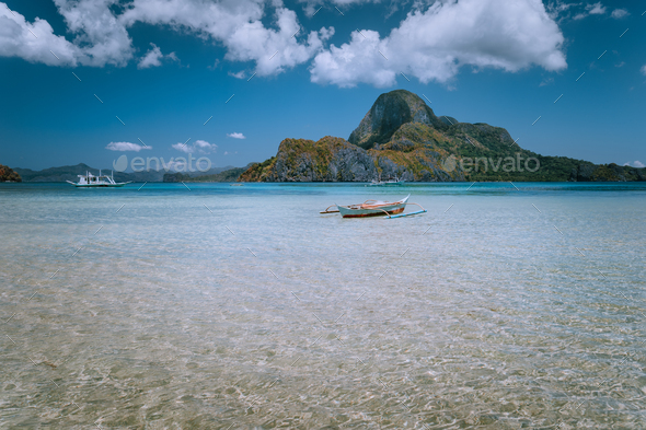 Panoramic view of blue lagoon with banca boat and Cadlao Island in background. Palawan, Philippines - Stock Photo - Images