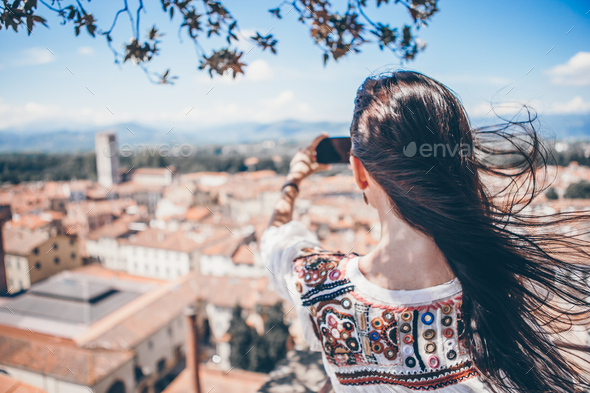 Young caucasian woman making photo by mobile phone from the observation place - Stock Photo - Images