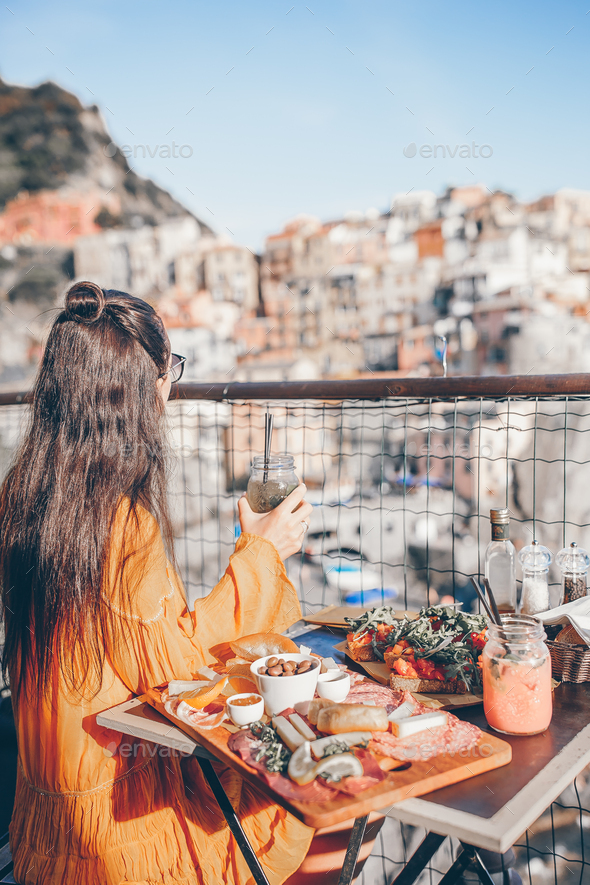 Beautiful woman on breakfast at outdoor cafe with amazing view in Cinque Terre - Stock Photo - Images