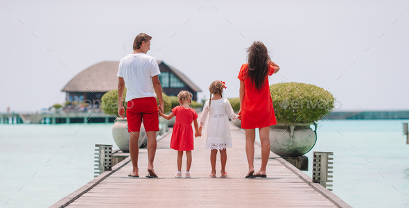 Family of four on beach vacation have fun - Stock Photo - Images