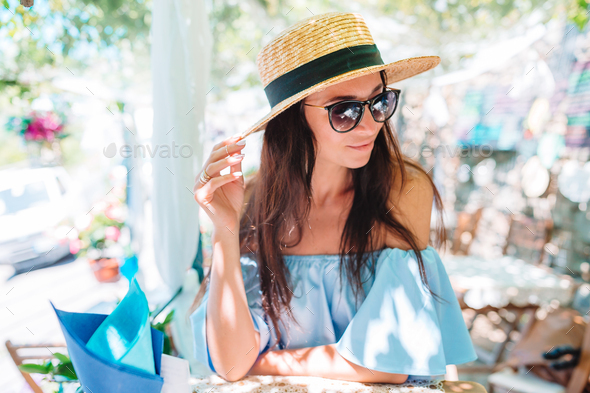 Portrait of young beautiful woman sitting in a cafe outdoor drinking coffee - Stock Photo - Images