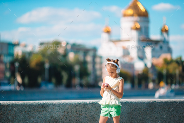 Little adorable girl listening music in the park - Stock Photo - Images