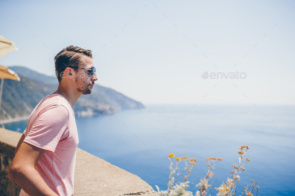 Back view of young man background stunning village. Tourist looking at scenic view of Manarola - Stock Photo - Images