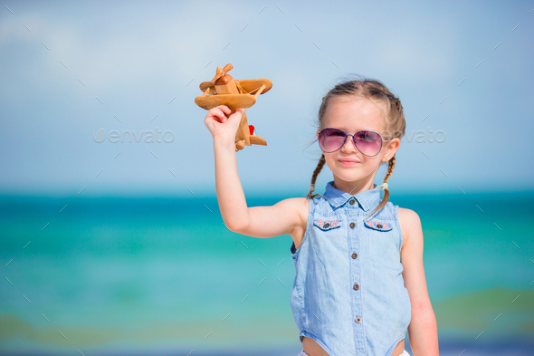 Happy little girl with toy airplane in hands on white sandy beach - Stock Photo - Images