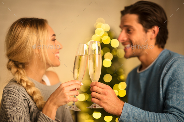 Happy couple with glasses of champagne celebrating Christmas - Stock Photo - Images