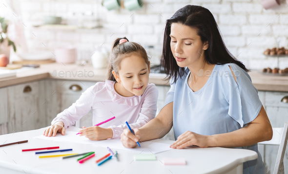 Mom teaching her little daughter how to draw - Stock Photo - Images