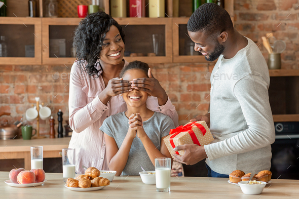 Lovely parents giving their daughter gift during breakfast - Stock Photo - Images