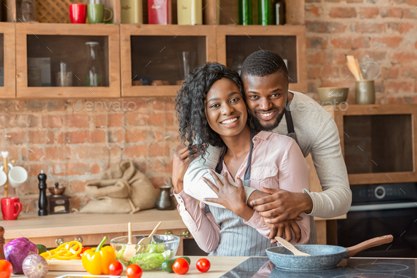 Cheerful black man hugging his wife while cooking at kitchen - Stock Photo - Images