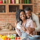 Cheerful black man hugging his wife while cooking at kitchen - PhotoDune Item for Sale