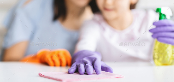 Little girl and her mom cleaning table surface from dust - Stock Photo - Images