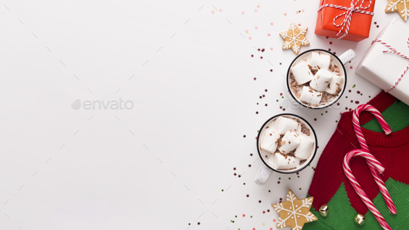 Two cacao cups with candy canes and red sweater with pine trees - Stock Photo - Images