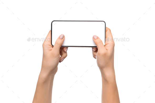 Female hands holding smartphone with blank screen, playing video games - Stock Photo - Images