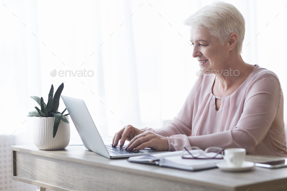 Professional business woman typing email to client - Stock Photo - Images