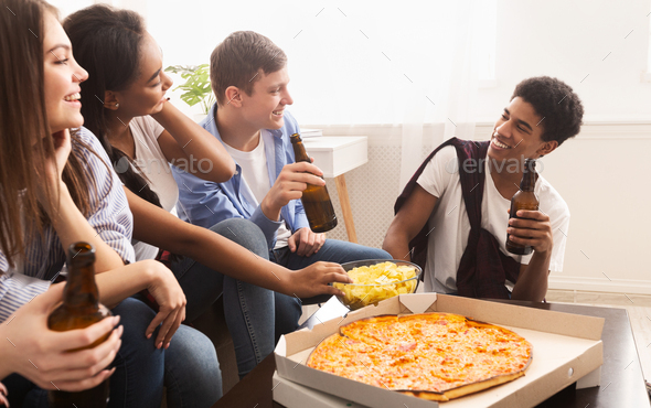 Happy friends meeting together, eating pizza at home - Stock Photo - Images