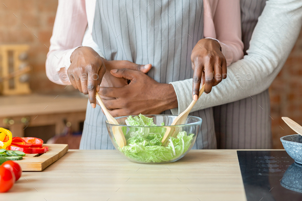 Cropped image of married couple cooking together at kitchen - Stock Photo - Images