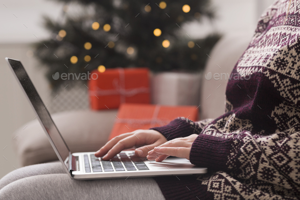 Woman in warm sweater with patterns searching Christmas presents - Stock Photo - Images