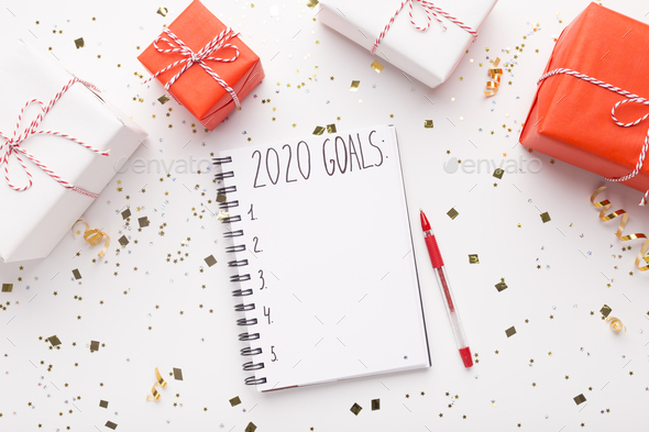 Notepad with goals and Christmas presents on white - Stock Photo - Images
