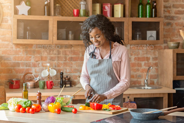 Pretty woman making veggies salad at kitchen - Stock Photo - Images