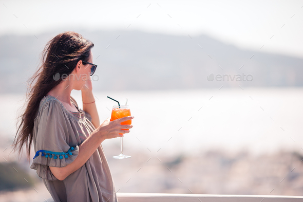 Young happy woman in outdoor cafe with tasty drink - Stock Photo - Images