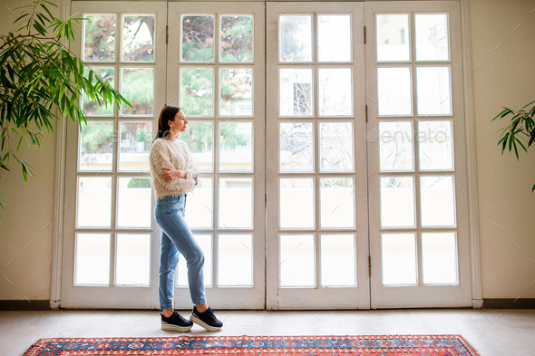 Beautiful girl on the terrace looks in a large window in a cozy boutique hotel - Stock Photo - Images