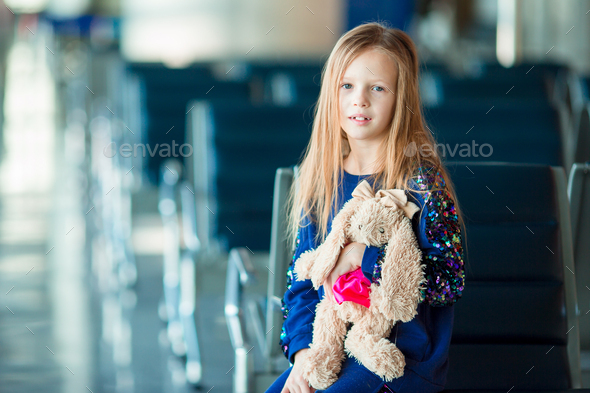 Little adorable girl in airport near big window with her favourite toy ready for travel - Stock Photo - Images