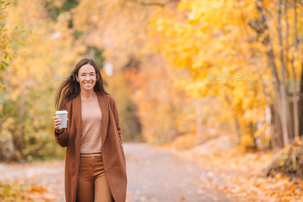 Fall concept - beautiful woman drinking coffee in autumn park under fall foliage - Stock Photo - Images
