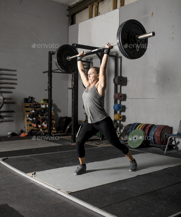 Strong femal weight lifter with heavy weights over her head, two thirds profile shot. - Stock Photo - Images