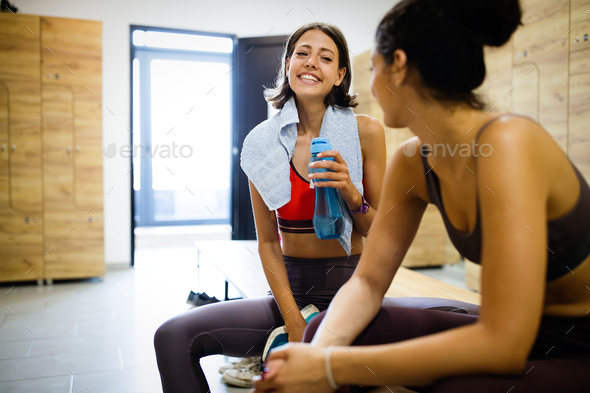 Happy friends enjoying break while chatting in the gym - Stock Photo - Images