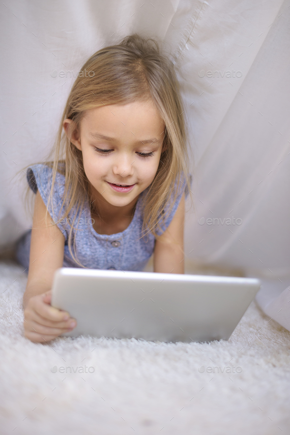 Girl affectionated with a digital tablet - Stock Photo - Images