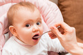Small baby girl while being fed with her mouth open - PhotoDune Item for Sale