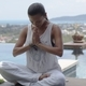 Relaxed barefooted lady sitting in lotus position near swimming pool - PhotoDune Item for Sale