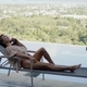 Woman lying on deckchair on top of hotel pool terrace - PhotoDune Item for Sale