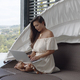 Adult barefooted woman using laptop on balcony against landscape at tropical resort - PhotoDune Item for Sale