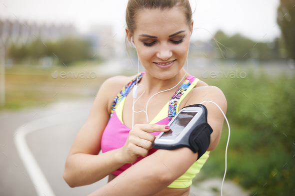 Turning on a playlist before the jogging - Stock Photo - Images