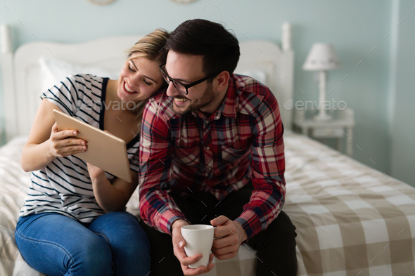 Young attractive couple using tablet in bedroom - Stock Photo - Images