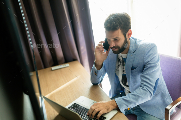 Portrait of successful young handsome man using laptop - Stock Photo - Images