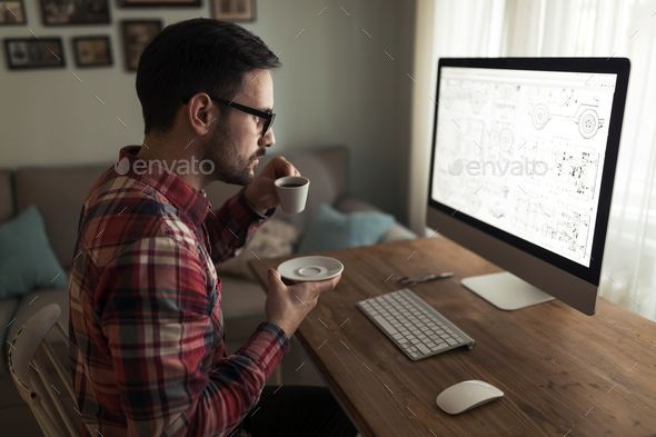 Young handsome designer working on project on computer - Stock Photo - Images