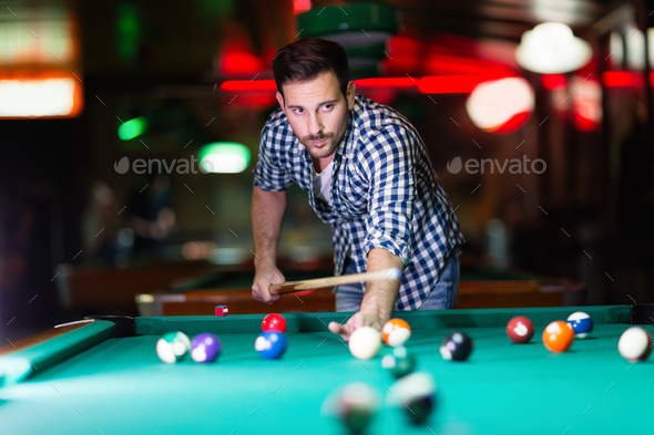 Hansome man playing pool in bar alone - Stock Photo - Images