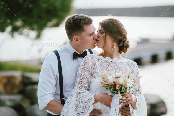 Happy newly married kissing couple, smiling bride brunette young woman with groom - Stock Photo - Images