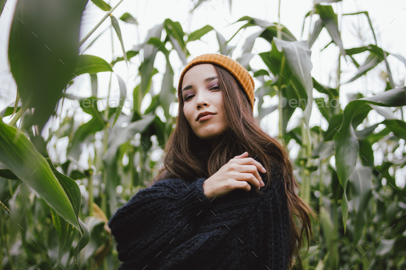 Beautiful carefree long hair asian girl in yellow hat and knitted sweater in autumn corn field - Stock Photo - Images