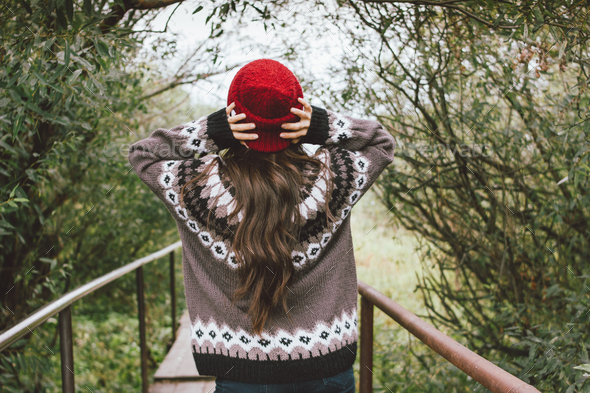 Long hair asian girl in red hat and knitted nordic sweater in autumn nature park - Stock Photo - Images