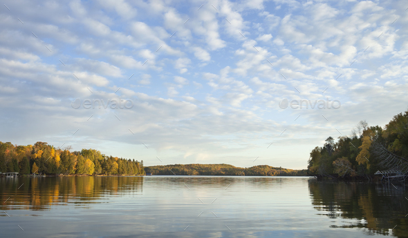 Panorama of a lake in northern Minnesota with clouds and blue sky on a bright morning during autumn - Stock Photo - Images