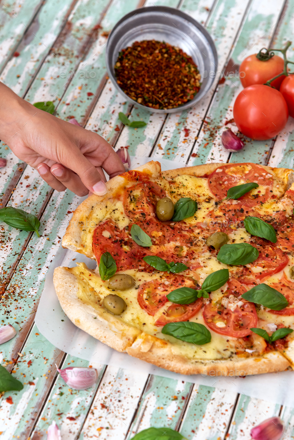 Hand of a woman taking a slice of a pizza viewed from above - Stock Photo - Images