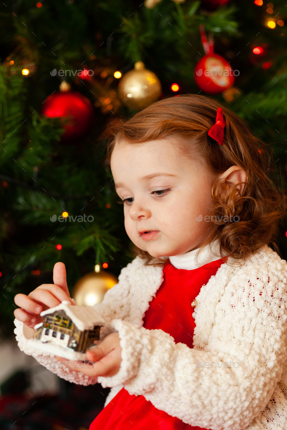 Beautiful little child near Christmas tree. - Stock Photo - Images