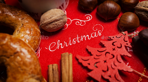 Merry Christmas text on a tablecloth with Christmas food - Stock Photo - Images